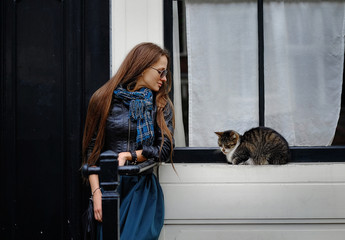 Portrait of a girl, model with a cat on the porch near the house. Portrait, style, tenderness.