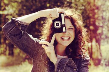 jeune femme souriante photographiant avec appareil photo vintage hipster