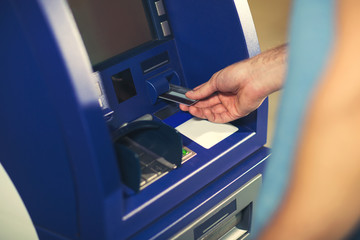 Man uses an ATM card inserted into the ATM machine for cash..