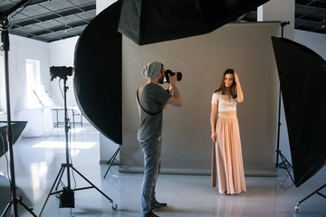 Photographer work in professional studio . Man taking shot of female model. Photo school, lookbook, fashion backstage concept