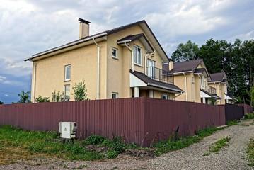Серые современные дома за коричневым железным забором
