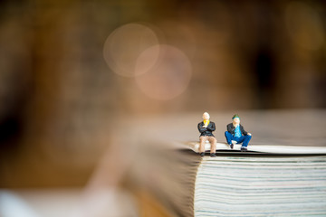 miniature people sitting on the corner of the book. using as education concept