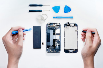 The smartphone was damages and need to repair  which tools smartphone that stand isolated on white background by hands of repairman. Wall mural