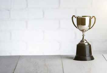 trophy over wooden table against white brick wall with Text Space