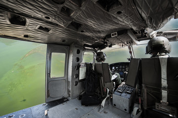 The image blurred of Cockpit interior details of Army helicopter with pilot and co pilot on board while flying over river. Pilot prepares to landing.