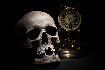 Human skull with vintage clock close up on black background