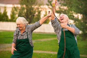 People having fun, water hose. Cheerful old couple outdoor.