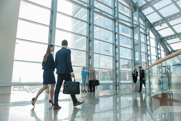 Business people walking in glass building