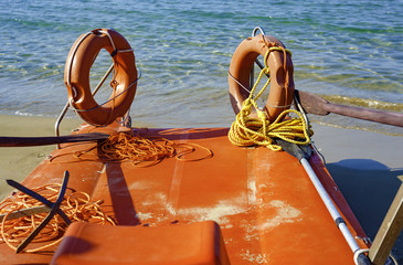 Close up lifeboat on the beach. The sea is calm and the bathers are at sea