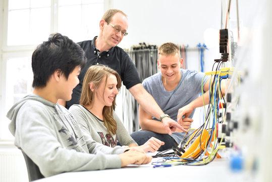 technische Berufsausbildung - Ausbilder mit jugendlichen Azubis im Unterricht an der Berufsschule // trainers with young apprentices