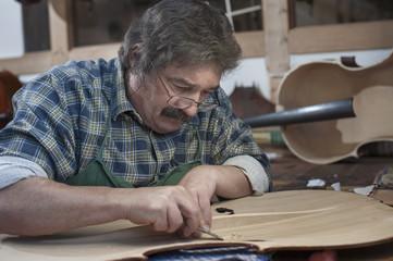 Craftsman in workshop carving violin