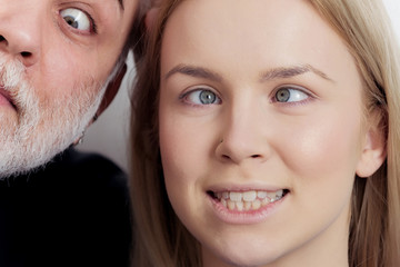 Girl and man squinting eyes on silly faces