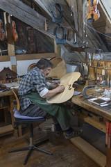 Craftsman working on violin in workshop