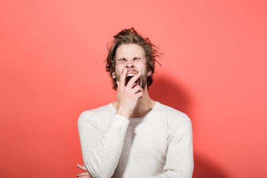 sleepy yawning man with long uncombed hair, morning wake up