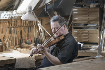 Violin maker playing violin while sitting in workshop