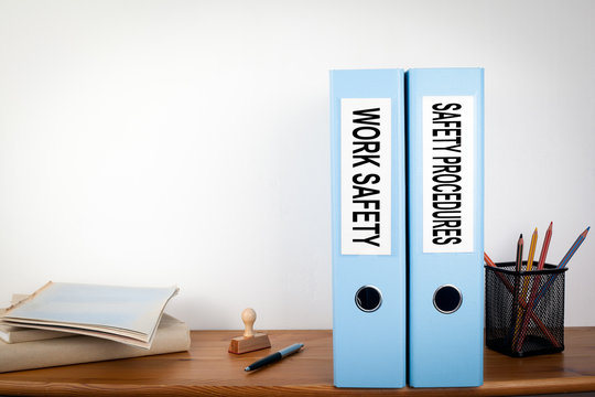 Work Safety and Safety Procedures binders in the office. Stationery on a wooden shelf.