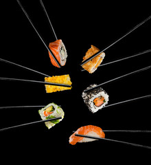 Sushi pieces placed between chopsticks, on black background