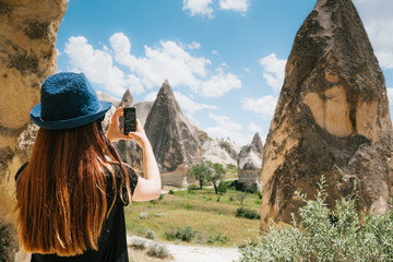 A tourist girl makes a photo on the phone in memory of a beautiful view of the hills in Cappadocia in Turkey. Travel, tourism, hiking, vacation.