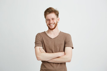 Portrait of happy cheerful young man with beard smiling looking at camera with crossed arms over white background. Wall mural