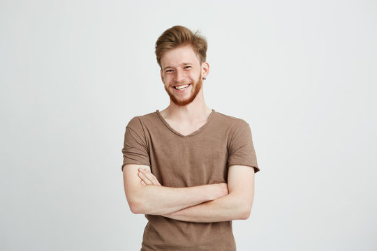 Portrait of happy cheerful young man with beard smiling looking at camera with crossed arms over white background.