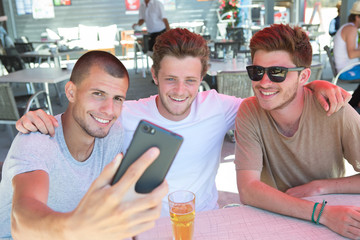appy male friends taking selfie and drinking beer at bar