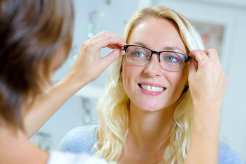 young woman trying on glasses in optical store
