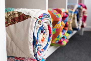 patchwork, sewing and fashion concept - bright finished quilts in the studio at white shelves with three storage compartments, the warehouse of finished products, side view, selective focus Fototapete
