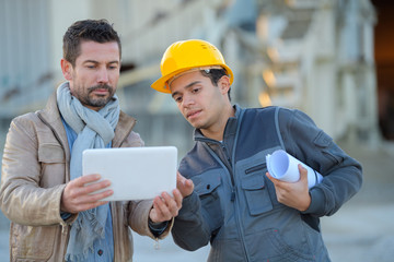 constructor and manager working on modern tablet outside renovated factory