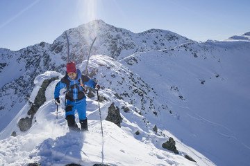 Skier walking on ridge of snow mountain