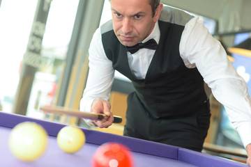 billiard player finding best angle at snooker pool