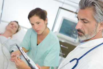 doctor and nurse with clipboards visiting patient woman at hospital