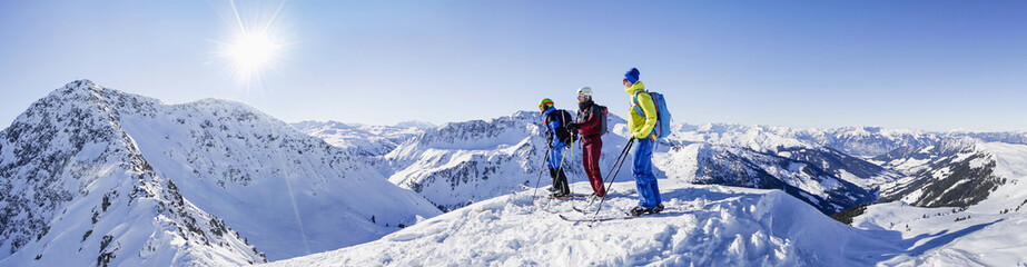 Three skiers standing on snowcapped mountain