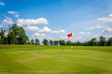 Golf course with beautiful green grass, bright blue skies and white puffy clouds.  Recreational sporting activity of golf.