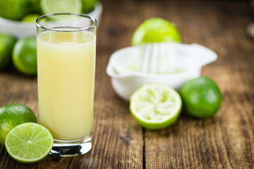 Portion of Fresh Lime Juice on wooden background (selective focus)
