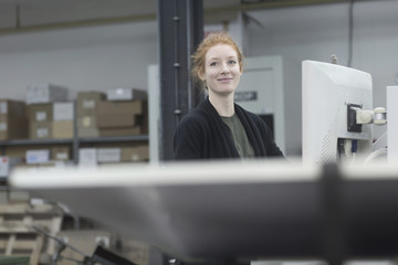 Smiling print worker working by printing equipment at press