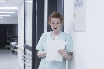Shocked nurse reading medical chart while leaning by wall