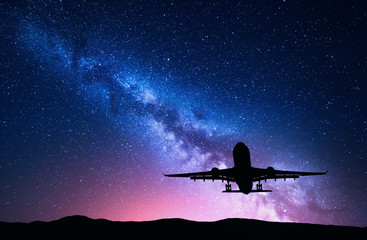Milky Way and silhouette of a airplane. Landscape with passenger airplane is flying in the starry sky at night. Space background. Landing airliner on the background of colorful Milky Way. Aircraft Wall mural