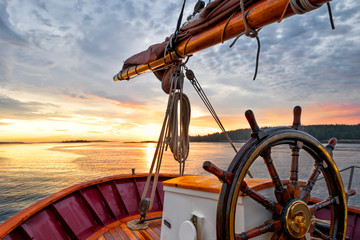 Foto op Aluminium Zeilen Sunrise sailing on a tall ship schooner. Close up of steering wheel, bow and boom against a dramatic sky at dawn.