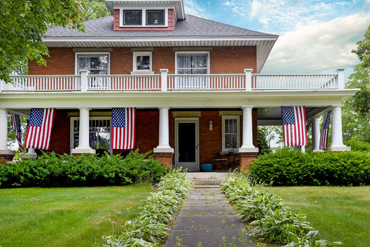 American flag decorations on front porch of old brick home