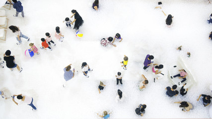 group of people play and run on the white bubble playground on the top aerial view.