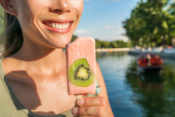 Healthy girl eating in city. Smiling woman enjoying ice pop snack in summer park in Beijing hutongs, near Houhai lake. Popular urban destination for romantic getaway in china.