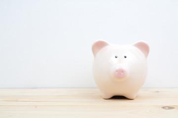 a pink piggy bank on wood