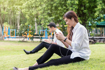 Happy asian couple listening the song via smart phone camera and using the laptop in the park, lover and lifestyle concept