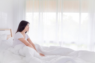 Beautiful asian girl resting on bed in morning