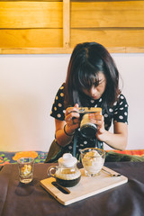 Young asian girl taking picture of Affogato ice cream in coffee shop.