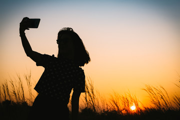 Silhouette of woman taking selfie during sunset with flowering grass