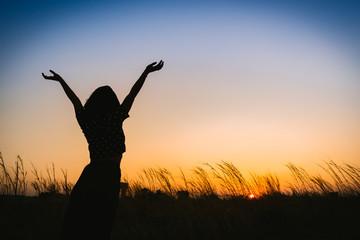 silhouette of woman open arms under the sunset