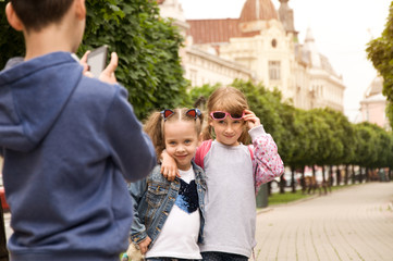 A group of children have a vacation in Europe. Children do selfie on the phone.