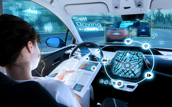 young woman reading a book in a autonomous car. driverless car. self driving vehicle. heads up display. automotive technology.