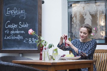 Young woman crushing pepper on salad at cafe by chalkboard